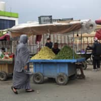 Street vendors wait for customers during a quarantine in the Muslim holy fasting month of Ramadan, in Kabul on Tuesday. Many South Asians are being left with a difficult choice: Buy a mask and let their family go hungry or buy food and go out into the crowded city without one. | AP