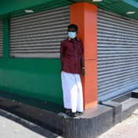 A man stands in front of closed shops in a street during a government-imposed nationwide lockdown in Colombo, Sri Lanka, on Sunday. | AFP-JIJI