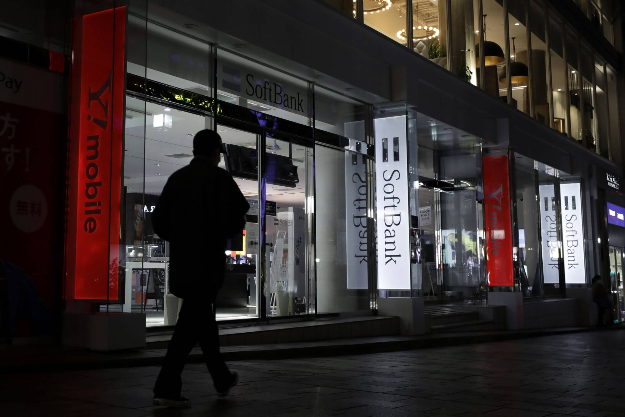 A pedestrian walks past illuminated signs for SoftBank displayed outside a store at night in Tokyo on April 14. | BLOOMBERG