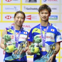 Arisa Higashino (left) and Yuta Watanabe stand on the podium during the award ceremony after earning bronze at the world championships in August of 2019. | KYODO