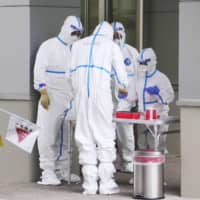 Doctors prepare for drive-through coronavirus testing on Monday in Koshigaya, Saitama Prefecture. Even after the state of emergency is lifted in Japan, experts agree that more testing will be crucial to permanently contain the virus. | KYODO