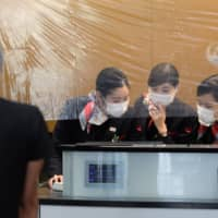 Japan Airlines Co. employees work behind a plastic sheet at a check-in counter at Haneda Airport in Tokyo last Thursday. | BLOOMBERG