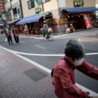 Elderly people wearing protective face masks walk are seen in Tokyo's Sugamo district, an area popular with Japan's seniors, on April 15 after the government declared a state of emergency for the capital and six other prefectures amid the coronavirus outbreak. | REUTERS