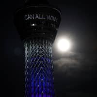The full moon is seen next to Tokyo Skytree, which is displaying a message reading 'Together we can all win' and illuminated in blue to honor first responders and essential workers as the coronavirus outbreak. | REUTERS