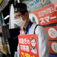 An employee of an electronics retail store wears a protective face mask and a face shied in Tokyo on May 9. | REUTERS