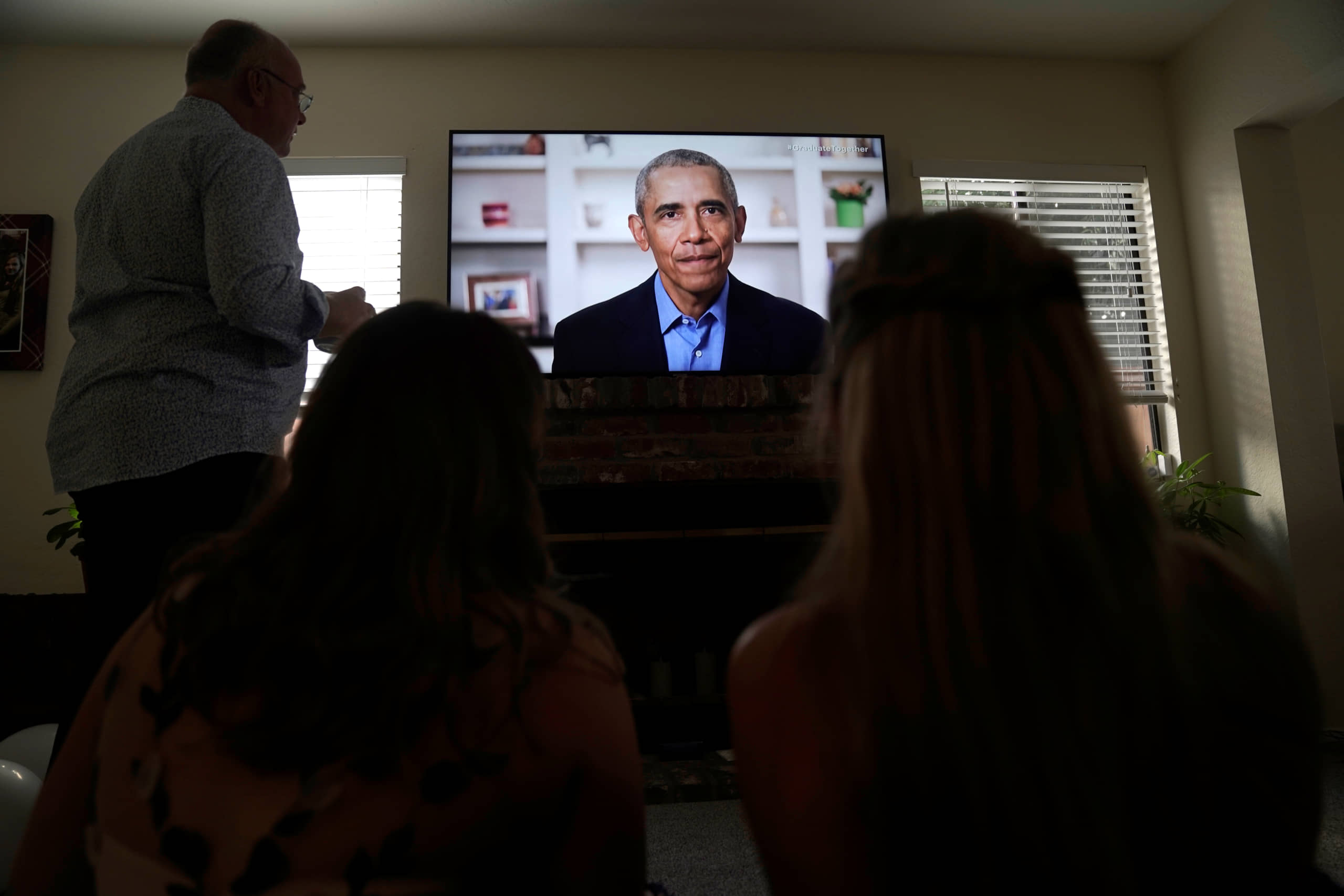 Torrey Pines High School graduating student Phoebe Seip, 18 (right), her father, Jake, 57, and her sister, Sydney, 22, watch former U.S. President Barack Obama deliver a virtual commencement address to millions of high school seniors who will miss graduation ceremonies due to the coronavirus pandemic, while celebrating Phoebe's canceled prom night at home in San Diego on Saturday. | REUTERS