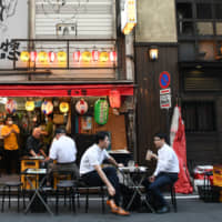 Customers dine at a Japanese-style pub in Tokyo's Yurakucho district on Friday. | BLOOMBERG