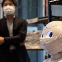 Pepper the robot wears a face mask as it stands in a hotel lobby during the first day the building is used as a new medical lodging facility to accommodate COVID-19 patients in Tokyo on May 1. | AFP-JIJI