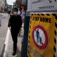 People walk on a street next to a 'stay home' notice as a preventive measure against coronavirus in Tokyo on May 12. | AFP-JIJI