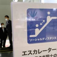 A sign reminding customers of social distancing rules to help stop the spread of COVID-19 is displayed at Tokyo's Seibu Ikebukuro department store, which resumed business for the first time in 46 days on Saturday. | AFP-JIJI