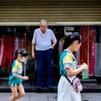 A man looks out from his shop toward two children in the Chinatown area of Yokohama on Tuesday after the government completely lifted a nationwide state of emergency over the coronavirus a day earlier. | AFP-JIJI