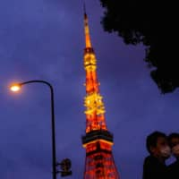 People wearing face masks take selfies in front of Tokyo Tower on May 20. | AFP-JIJI