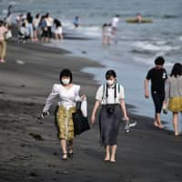 People walk on a beach in Kamakura, Kanagawa Prefecture, on Saturday, during the first weekend after the nationwide coronavirus state of emergency was lifted on May 25. | AFP-JIJI