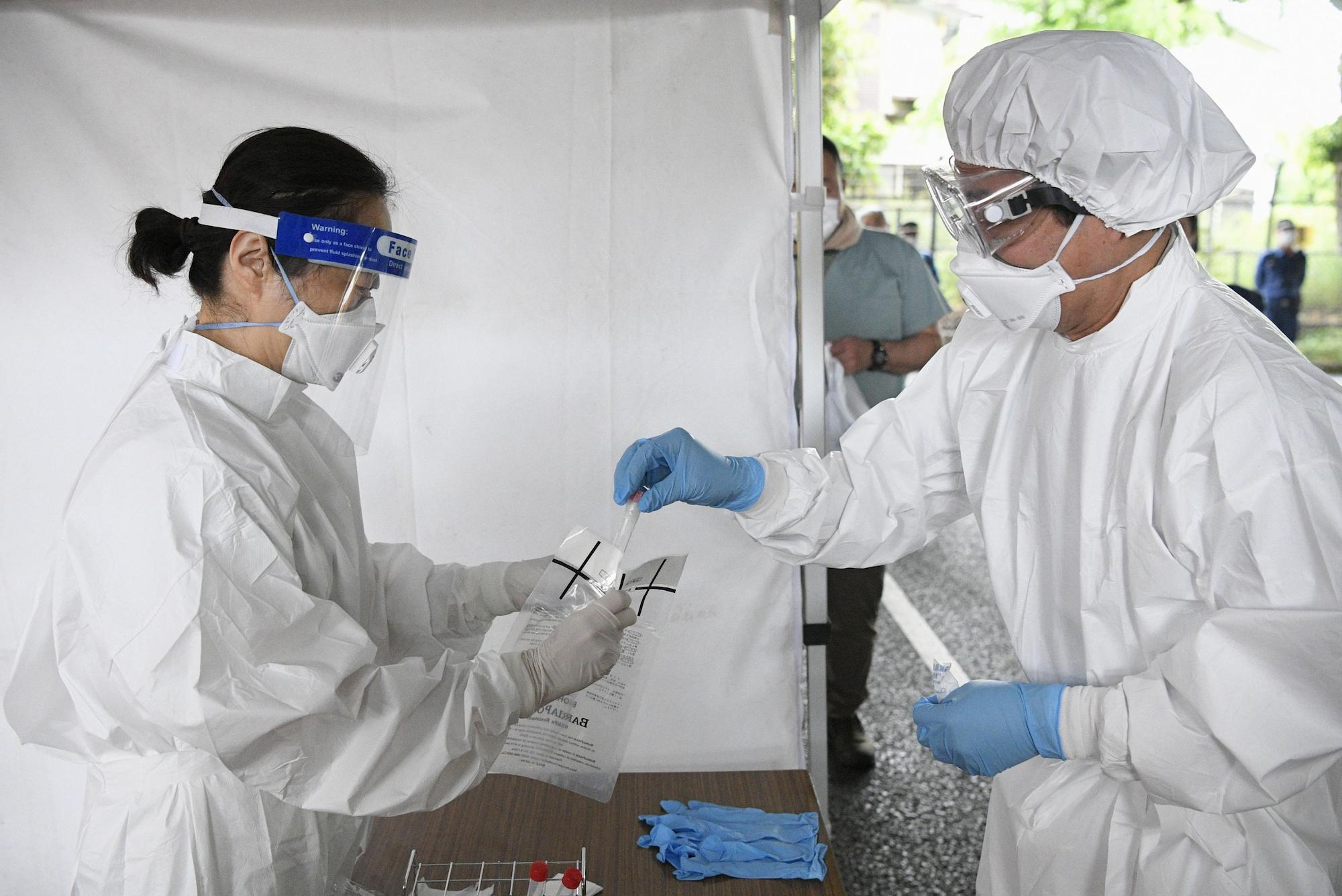 Medical workers practice processing a polymerase chain reaction (PCR) test at a drive-thru facility in Chofu in western Tokyo on May 20. | KYODO
