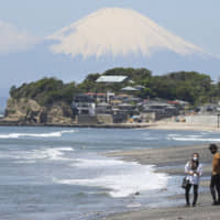 A couple wearing face masks walk on a beach in Kamakura with Mount Fuji in the background on May 7. | AP