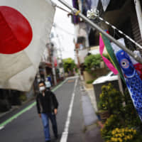 A man with a face mask walks near a Japanese national flag and colorful carp streamers to celebrate Children's Day on Tuesday in Tokyo. | AP
