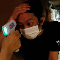 An restaurant employee has his temperature checked before his shift in Tokyo on Friday. | REUTERS