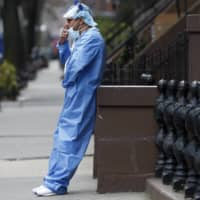 An emergency room nurse leans against a stoop as he takes a break from his work at the Brooklyn Hospital Center on April 5 in New York.   AP