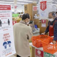 A clear acrylic board separates a cashier and customers at a do-it-yourself store in Fukuoka on April 9 in the middle of the coronavirus crisis. | KYODO