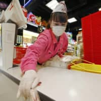 A cashier wearing a face mask and gloves disinfects a table at a supermarket in Osaka on April 9 due to the new coronavirus pandemic. | KYODO