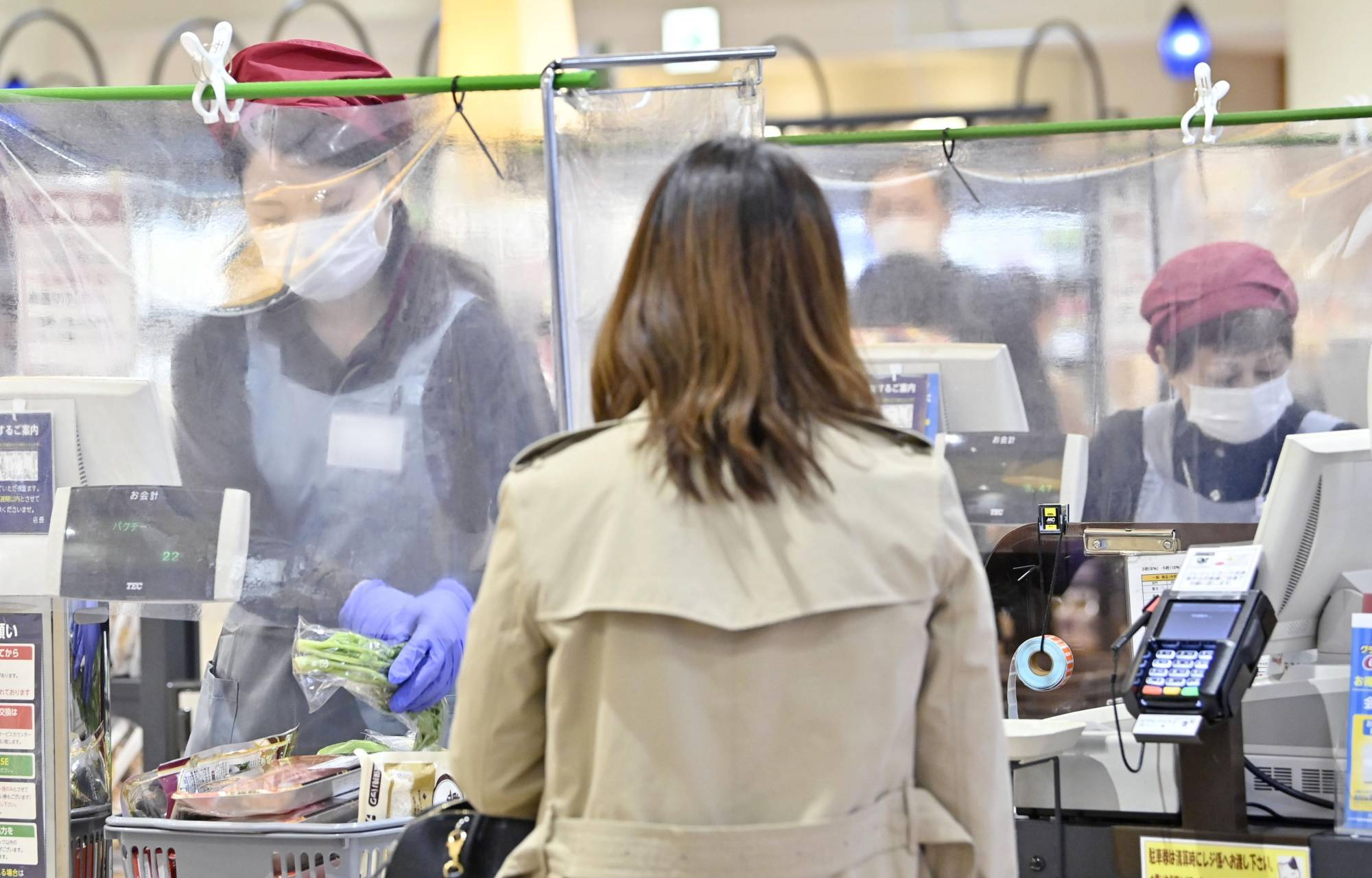 Cashiers work behind plastic drapes at a supermarket in Nagoya on April 24 amid the new coronavirus pandemic. | KYODO