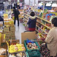 Customers keep their distance at a grocery store in Tokyo on April 22 amid the spread of the new coronavirus. | KYODO