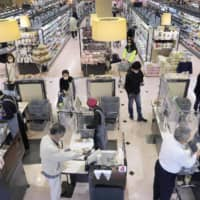 Cashiers work at a supermarket in Nagoya with transparent vinyl sheets separating them from customers to prevent the spread of the new coronavirus on April 24. | KYODO
