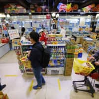 People stand in a checkout line while keeping distance from each other at a supermarket in Osaka on April 9 amid the spread of the new coronavirus. | KYODO