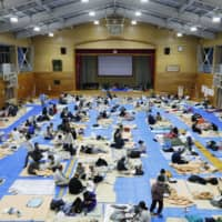 Evacuees shelter at a school gymnasium in the city of Nagano in October after major flooding caused by Typhoon Hagibis. | KYODO