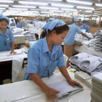 Employees work at a Japanese garment factory in Mingaladon Industrial Park in Yangon, Myanmar, in December 2011. | KYODO