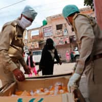 Policemen distribute free food during a nationwide lockdown in Agra, India, on April 23. The city is battling a second wave of infections.    REUTERS
