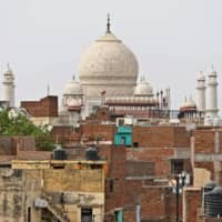 Children play on the roofs of their houses with the Taj Mahal in the background in Agra.    REUTERS