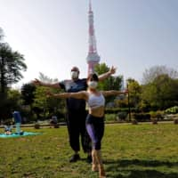 People wear protective face masks as they perform acroyoga at a park next to Tokyo Tower, amid the coronavirus outbreak, in Tokyo on Saturday. | REUTERS