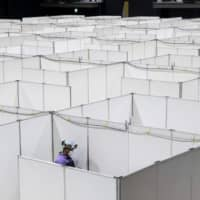 An employee helps set up a medical facility to accommodate coronavirus patients with mild symptoms at the Nippon Foundation Para Arena in Tokyo on Monday. | AFP-JIJI