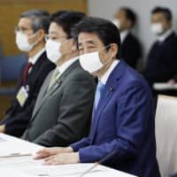 Prime Minister Shinzo Abe announces the extension of the state of emergency during a meeting of a government task force Monday. | KYODO