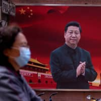 A woman wearing a protective mask walks past a portrait of Chinese leader Xi Jinping in Shanghai on March 12. | REUTERS