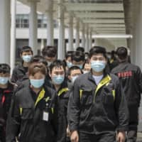 Employees wearing protective masks walk through the campus of the Geely Automobile Holdings Ltd. plant in Ningbo, Zhejiang Province, China, on Tuesday. Economic destruction and the coronavirus death toll are driving a U.S. government-wide push to move production and supply chain dependency away from China, current and former senior U.S. administration officials have said. | BLOOMBERG