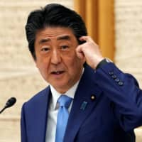 Prime Minister Shinzo Abe speaks during a news conference announcing an extension of the nationwide state of emergency, at the Prime Minister's Office in Tokyo on Monday. | POOL / VIA REUTERS
