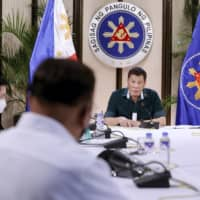 Philippine President Rodrigo Duterte (right) talks to Cabinet officials during a meeting in Manila on Monday. | MALACANANG PRESIDENTIAL PHOTOGRAPHERS DIVISION / VIA AP