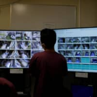 A medical worker monitors live footage of patients in the intensive care unit for COVID-19 in St. Marianna Medical University Hospital in Kawasaki on Monday. | REUTERS