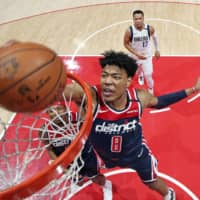 Rui Hachimura dunks against the Mavericks during a game in Washington. | NBA / VIA KYODO