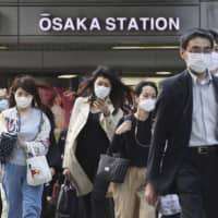 Commuters wearing face masks walk near Osaka Station on Thursday. | KYODO