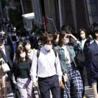 People wear masks as they commute during the morning rush hour Thursday in Tokyo. | AP