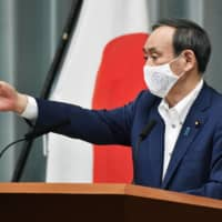 Chief Cabinet Secretary Yoshihide Suga attends a news conference on Thursday at the Prime Minister's Office in Tokyo.  | KYODO