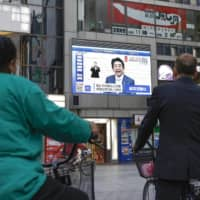 A screen shows Prime Minister Shinzo Abe explaining the extension of a nationwide state of emergency due to the coronavirus pandemic on May 4 in Osaka's Dotonbori district. | KYODO