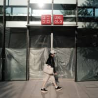 A person walks past a closed Uniqlo store in the Harajuku district in Tokyo on April 25. | BLOOMBERG
