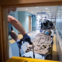 Medical personnel move an elderly non-COVID-19 patient from the hospital to a care home near Portsmouth, England, on Tuesday.   AFP-JIJI