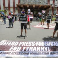 People from Bagong Alyansang Makabayan take part in a protest against the Philippine government-ordered shutdown of broadcaster ABS-CBN while observing social distancing outside the College of Mass Communication at the University of the Philippines in Manila on Friday. | AFP-JIJI