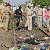 Police officers examine a railway track on Friday after a train ran over migrant workers sleeping on the track in the western Indian state of Maharashtra. | REUTERS