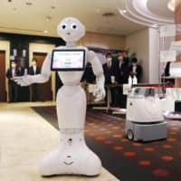 Pepper the robot greets customers in the lobby of a hotel in Hachioji, western Tokyo, reserved for coronavirus patients with mild or no symptoms. | KYODO